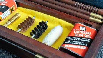 Gun cleaning accessories in a wooden case